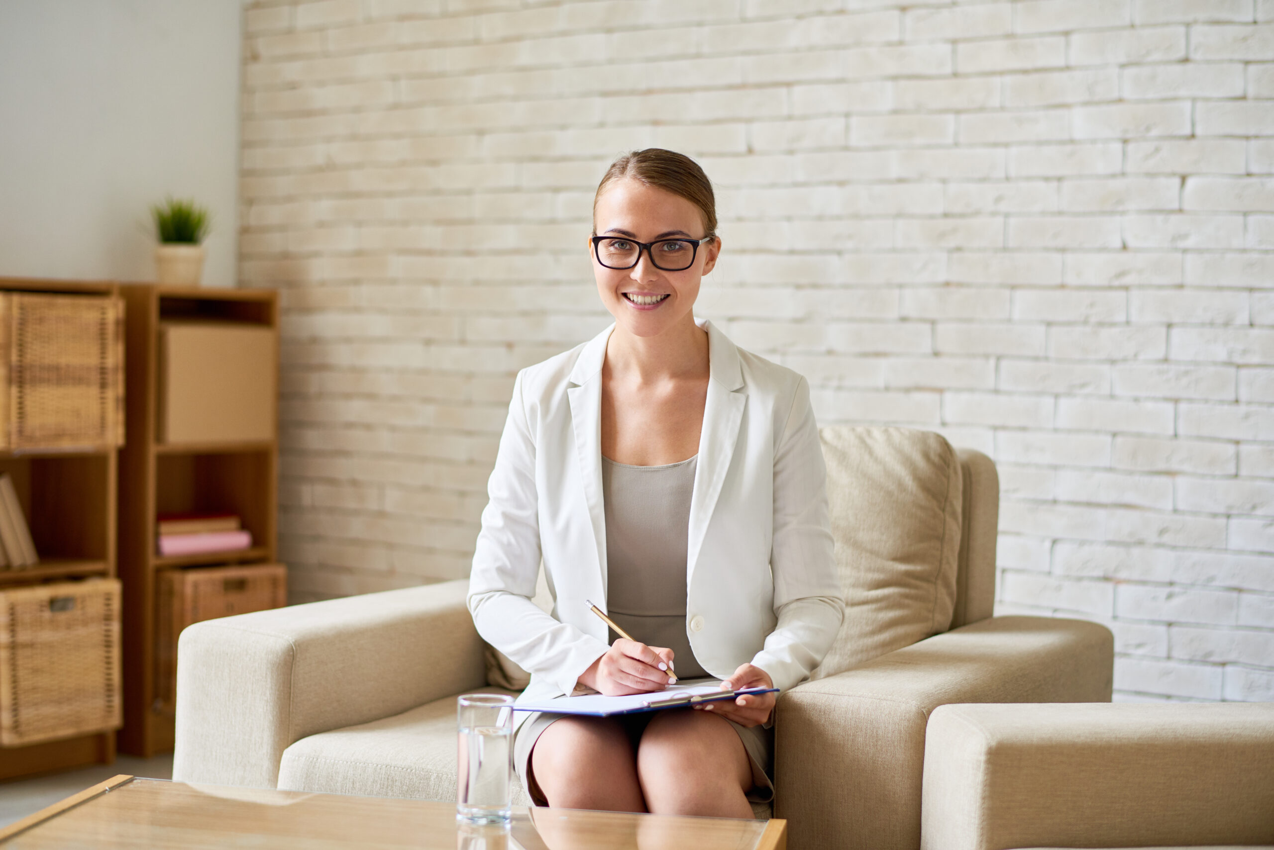 Portrait of beautiful young psychologist looking at camera with charming smile while taking notes on clipboard, interior of cozy office on background