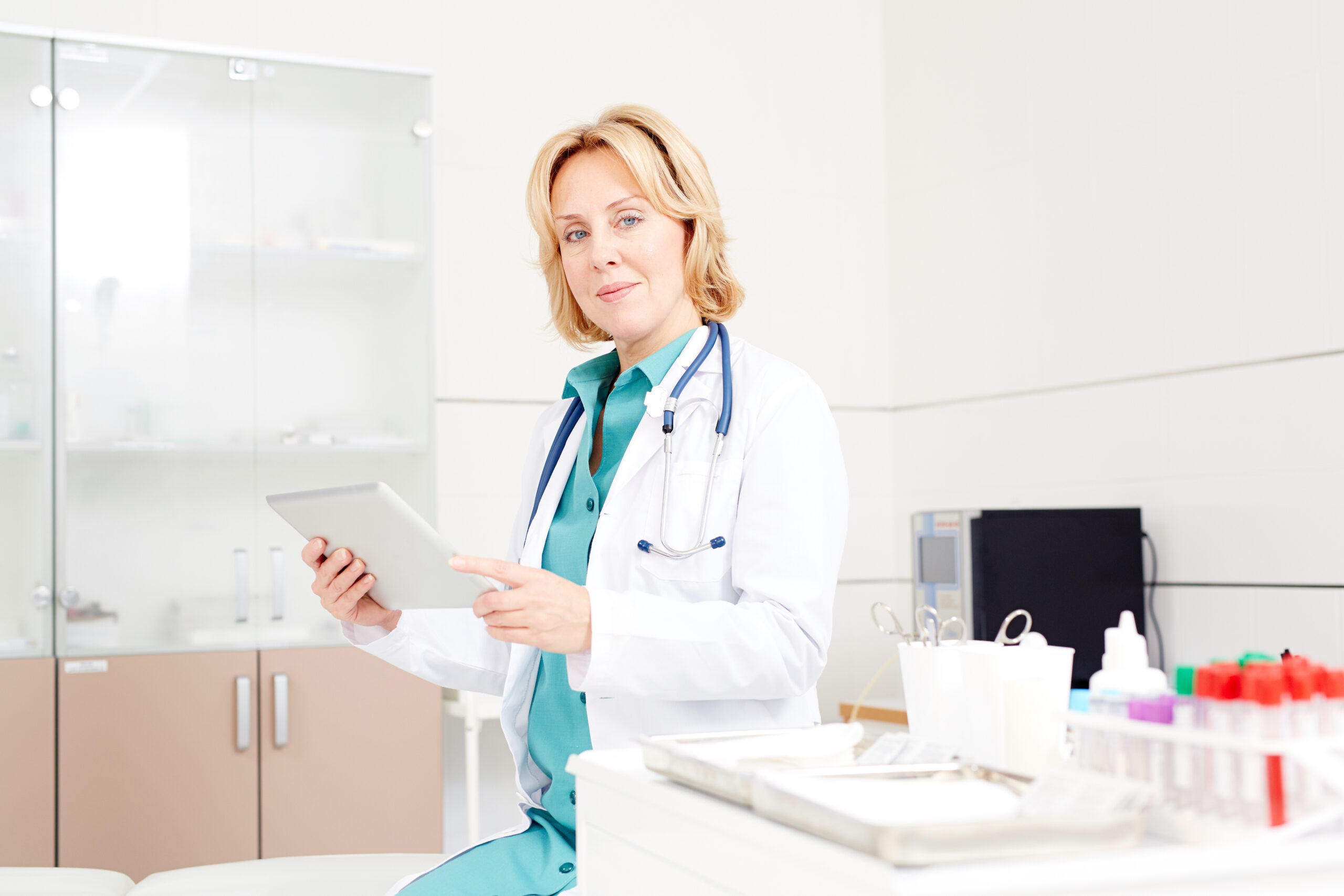 Modern doctor with touchpad working in the net in her office